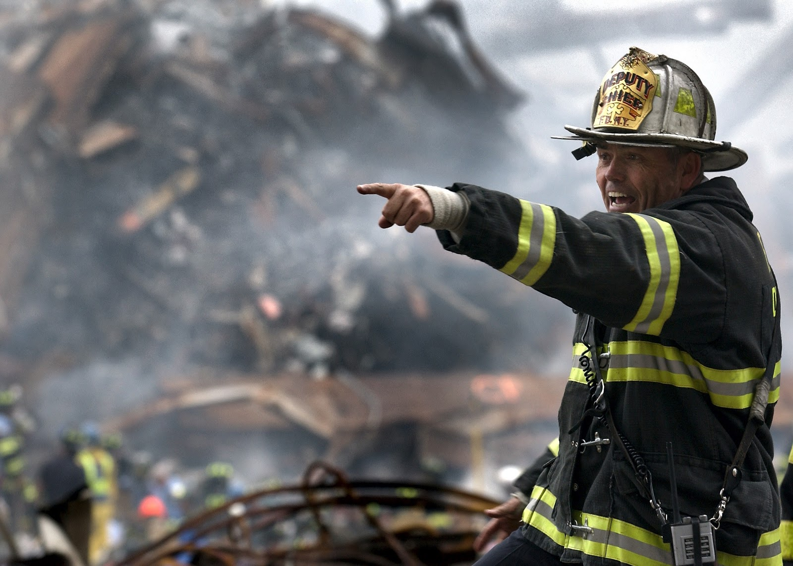 a fire fighter pointing while he stands in front of smoldering rubble