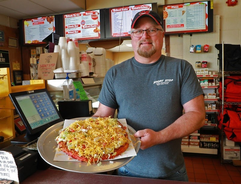 A worker at the local Ohio pizza shop KNS Short Stop shows us one of their signature pies.