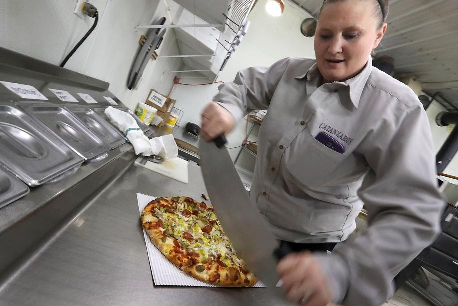 A woman wearing a grey uniform happily cuts a pizza in half with a large slicer.