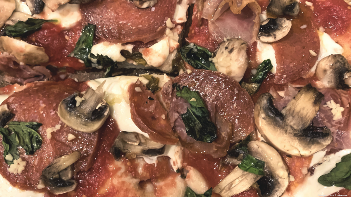 A blend of ingredients, like mushrooms, peperoni, cheese, and spinach, on the top of a pizza pie.