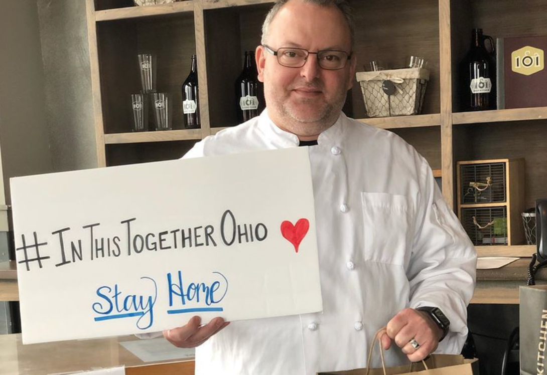 a columbus business owner offering takeout and holding a sign that reads In this together ohio -- stay healthy