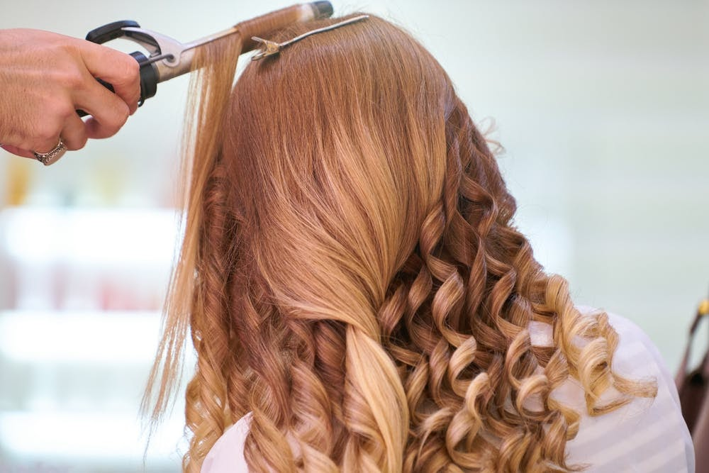 woman getting her hair curled