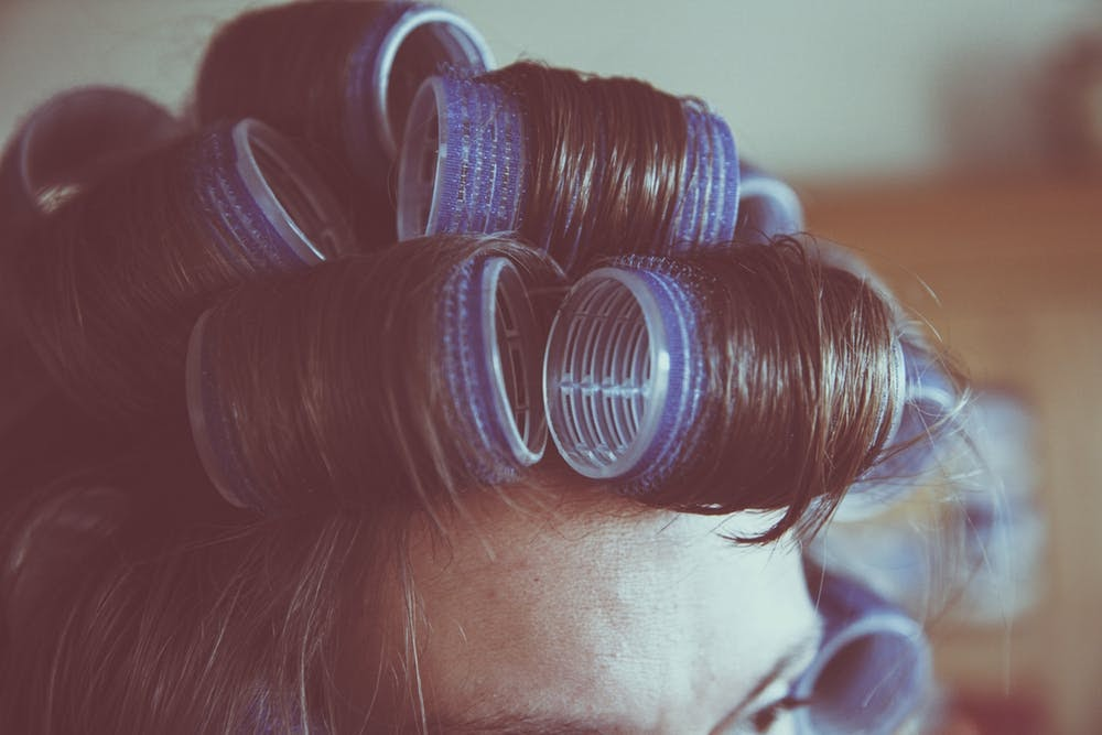 woman with hair curlers in