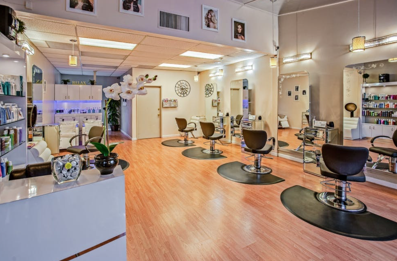 a hair salon with wooden floor and black stylist's chairs