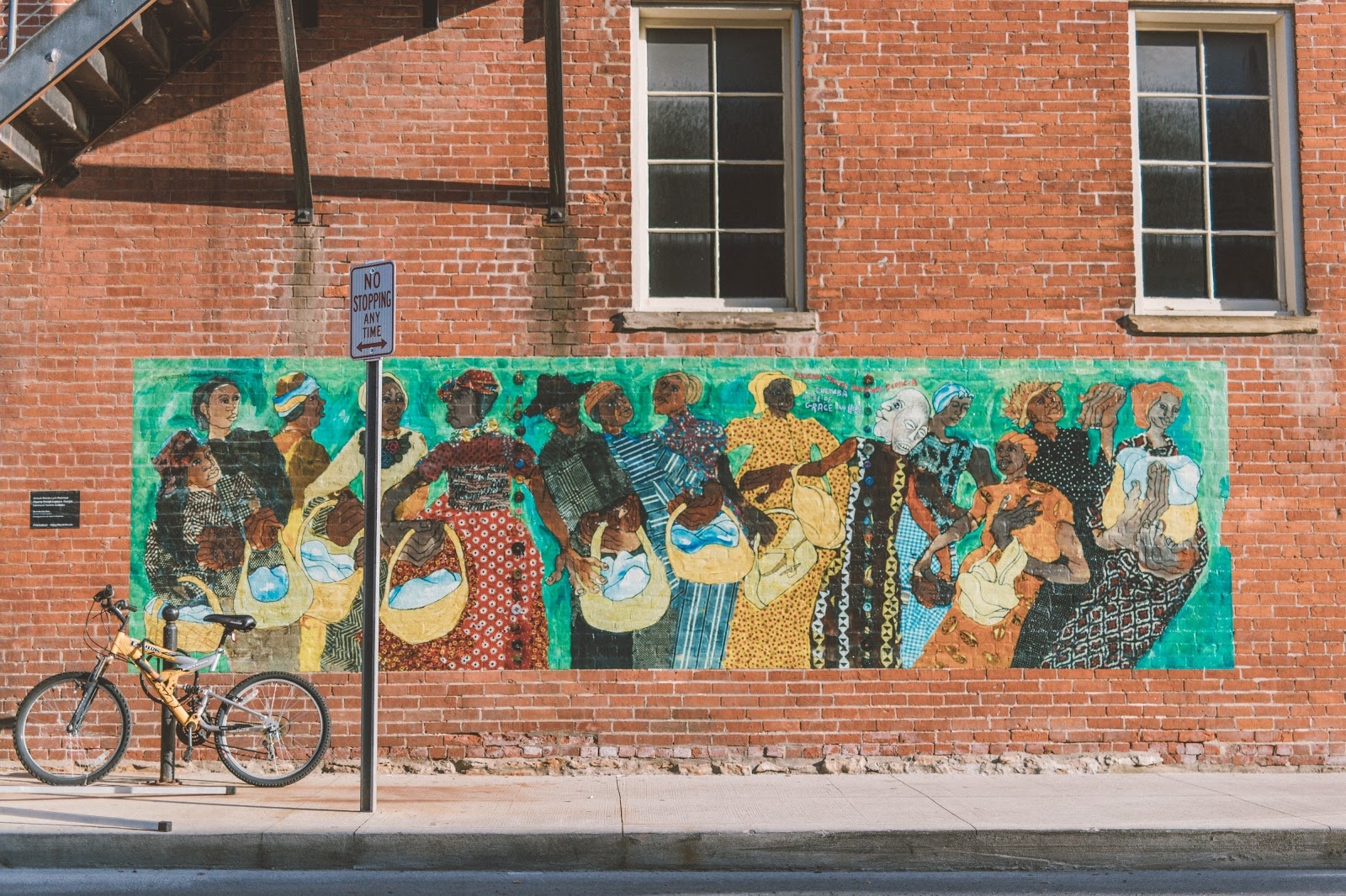 Mural of Black Women with baskets and various color outfits. This represents kinship and the Great Migration to the North.
