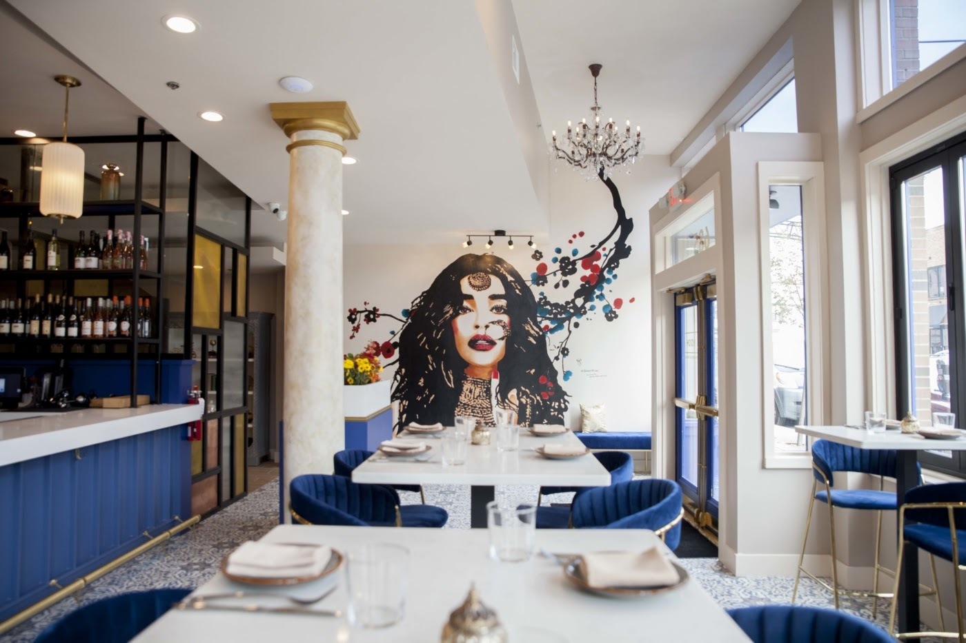 Rooh Winebar interior with a blue and gold motif. On the back wall is a mural of an Indian Woman portrait and floral design.