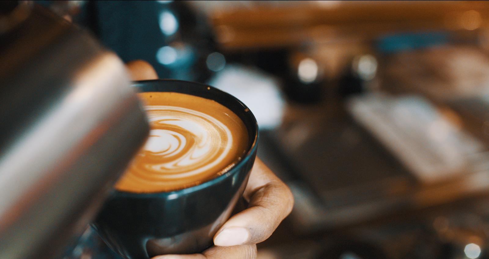 a barista pours cream into a latte