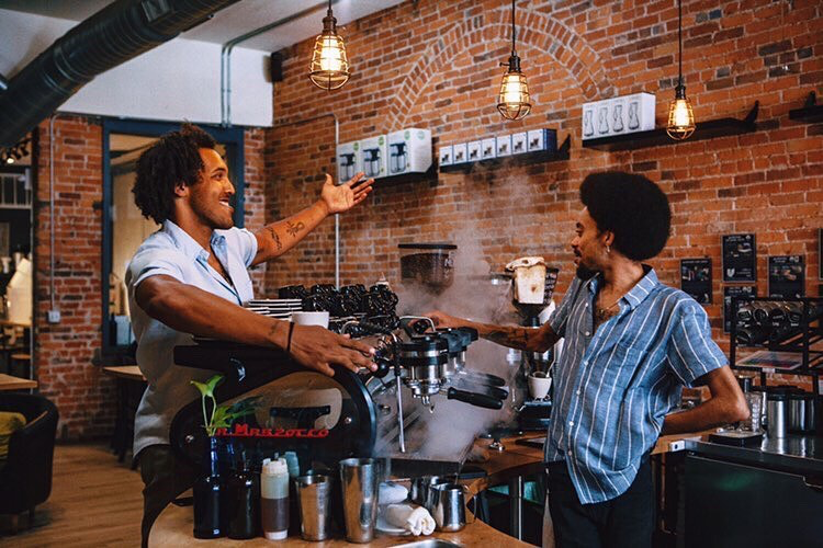 Stylish barista and customer interacting in front of brick wall in coffee shop setting