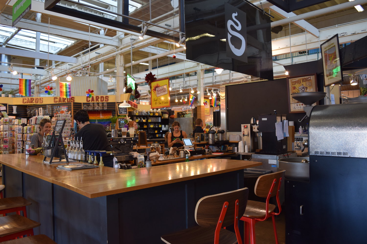 Bar-style kiosk with barista serving a customer, all inside a large public market