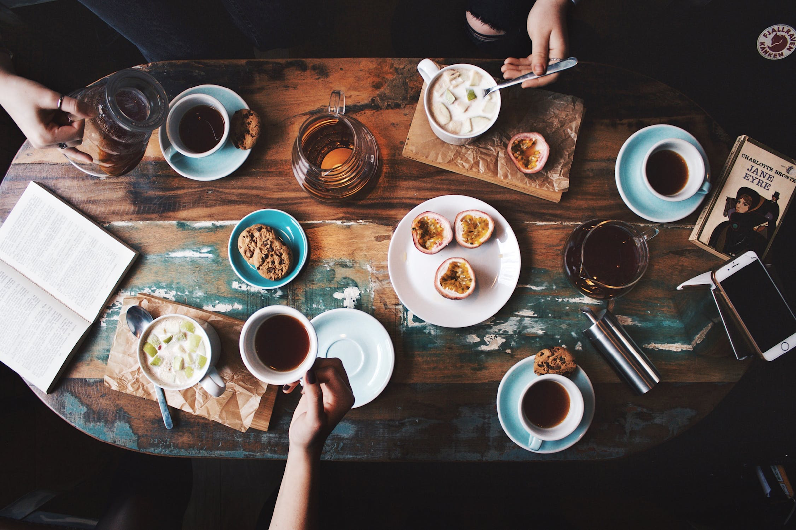 A lively overhead shot of table featuring coffee, books, pastries, and phones