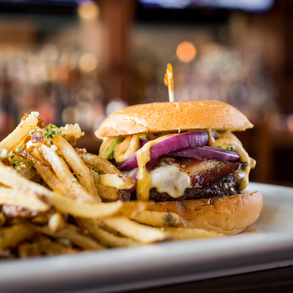 Burger with cheese and bacon alongside heaping pile of fries