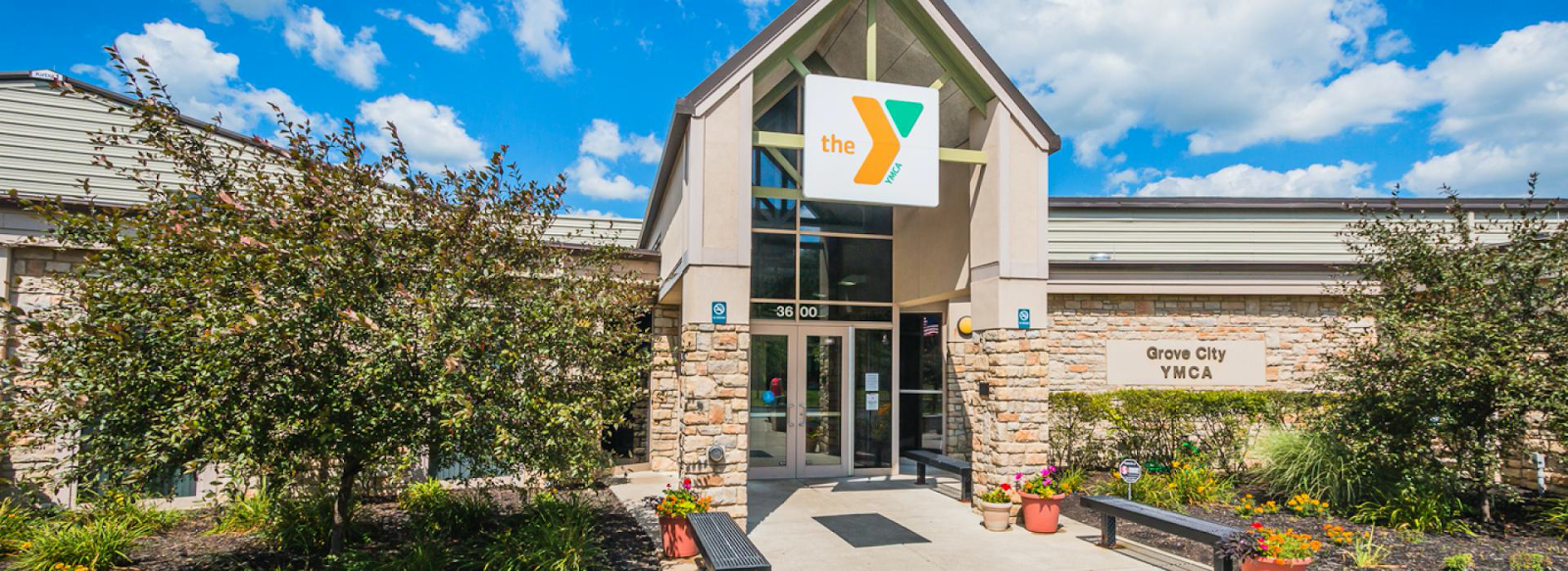 Outside of the Grove City YMCA. Build is long and made of stone.