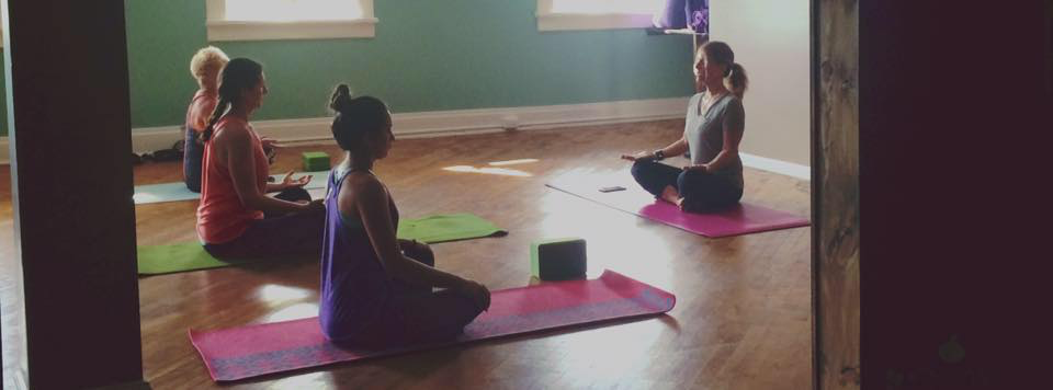 Photo of Yoga Class. Instructor is sitting the front in an upright position.
