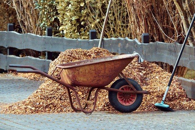 A wheelbarrow next to a large pile of mulch