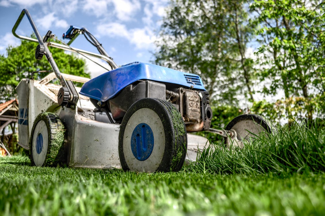 A blue lawnmower in the grass