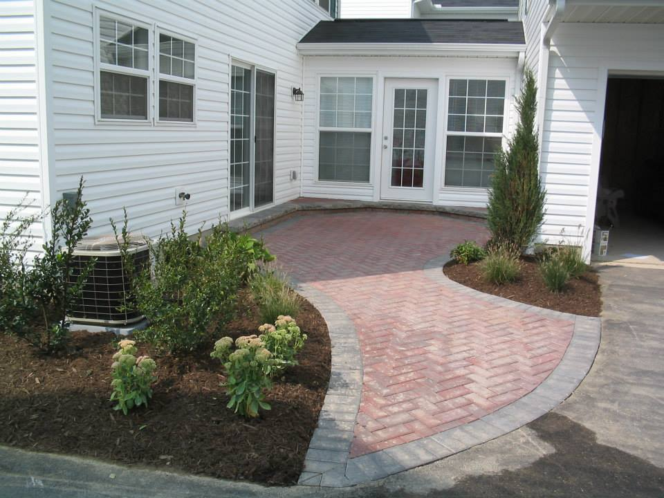 brick patio and bushes.