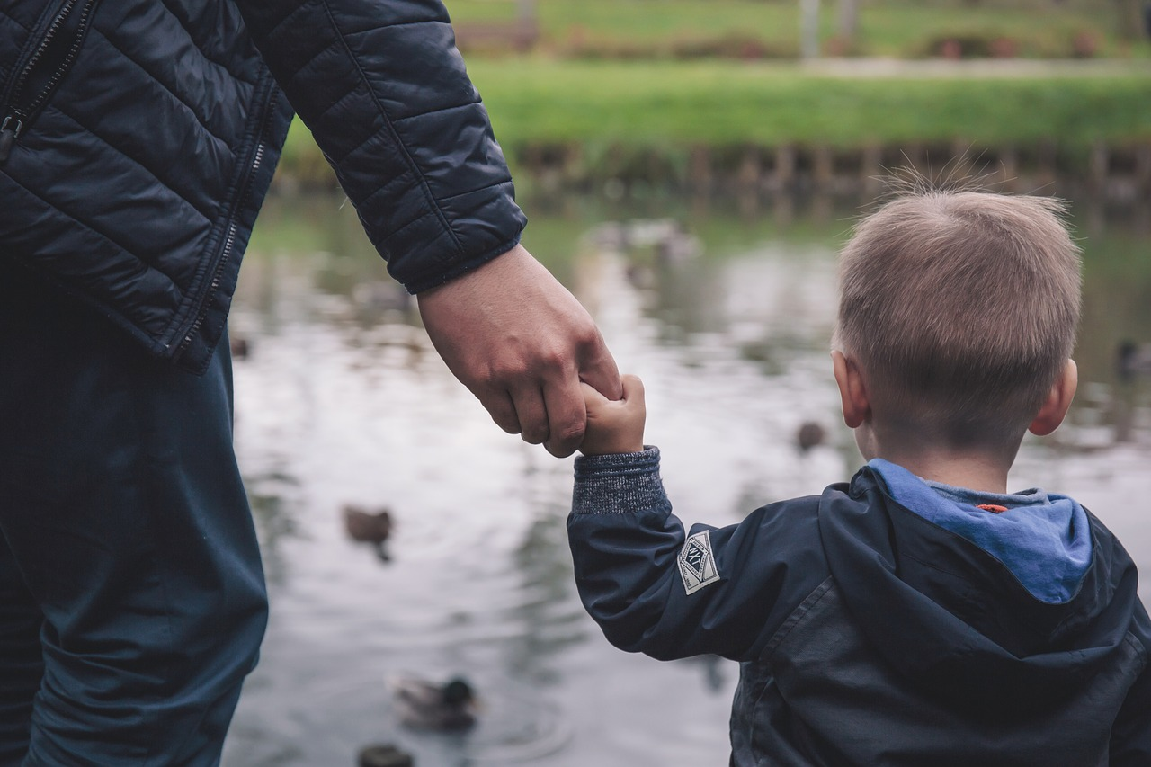 a father holding his child's hand by a pond