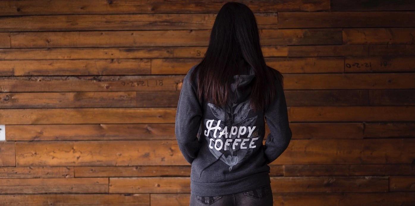 A woman's back in a Happy Coffee sweatshirt