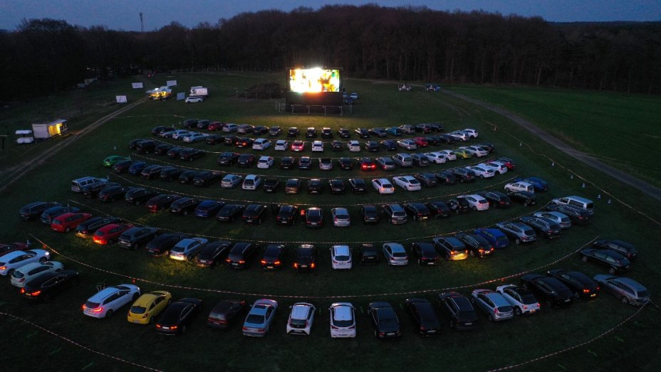 7 rows of cars lined up in front of a huge drive in movie screen.