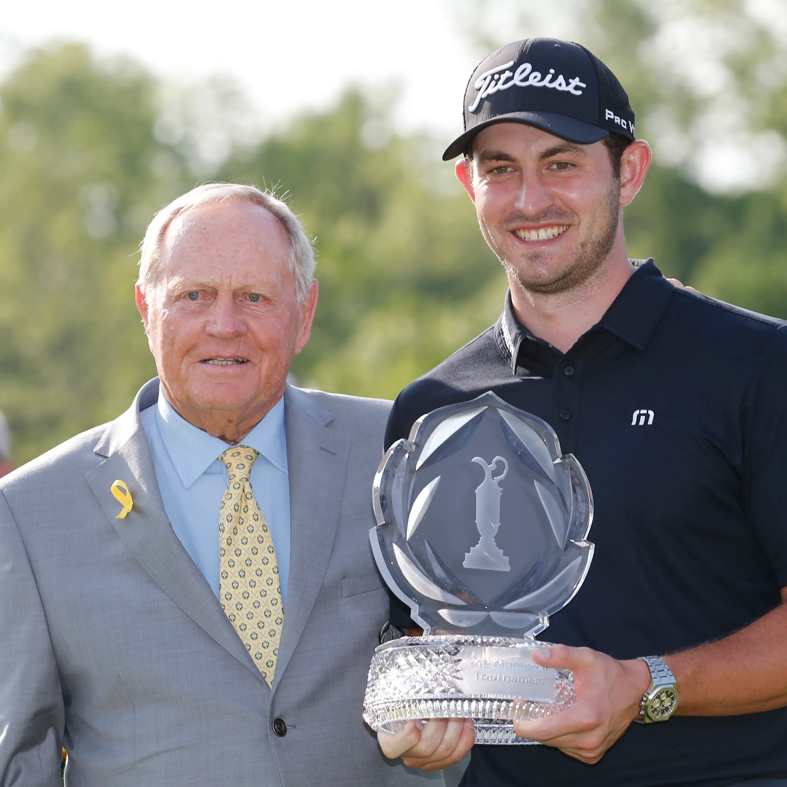 Jack Nicklaus featured with the winner of a previous Memorial Tournament while holding the trophy