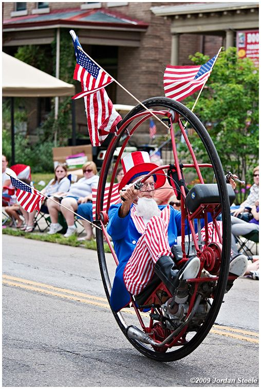 A man dressed up as Uncle Sam is featured riding a monocycle with flags coming out of the top