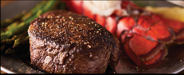 A close up of a steak and lobster dish