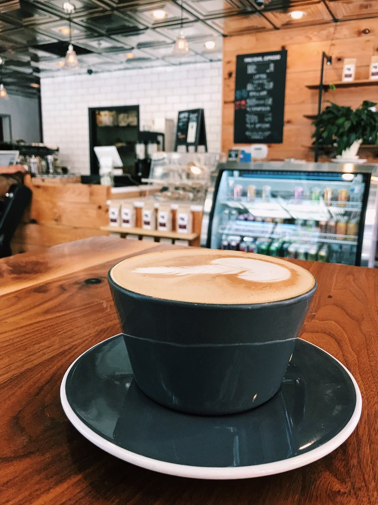 latte filled to the rim of a coffee cup. background includes the coffee shop and case full of other drink items