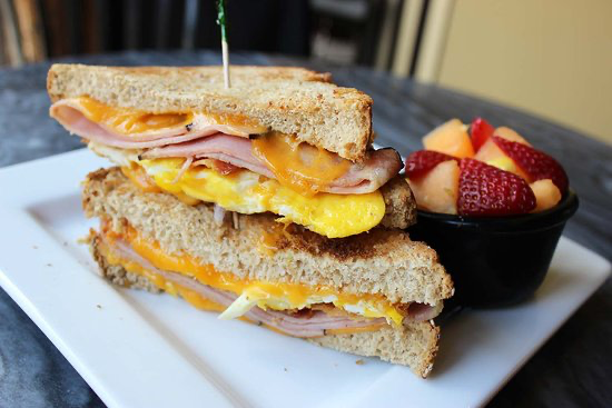A ham and cheese breakfast sandwich with a side of strawberries and melon.