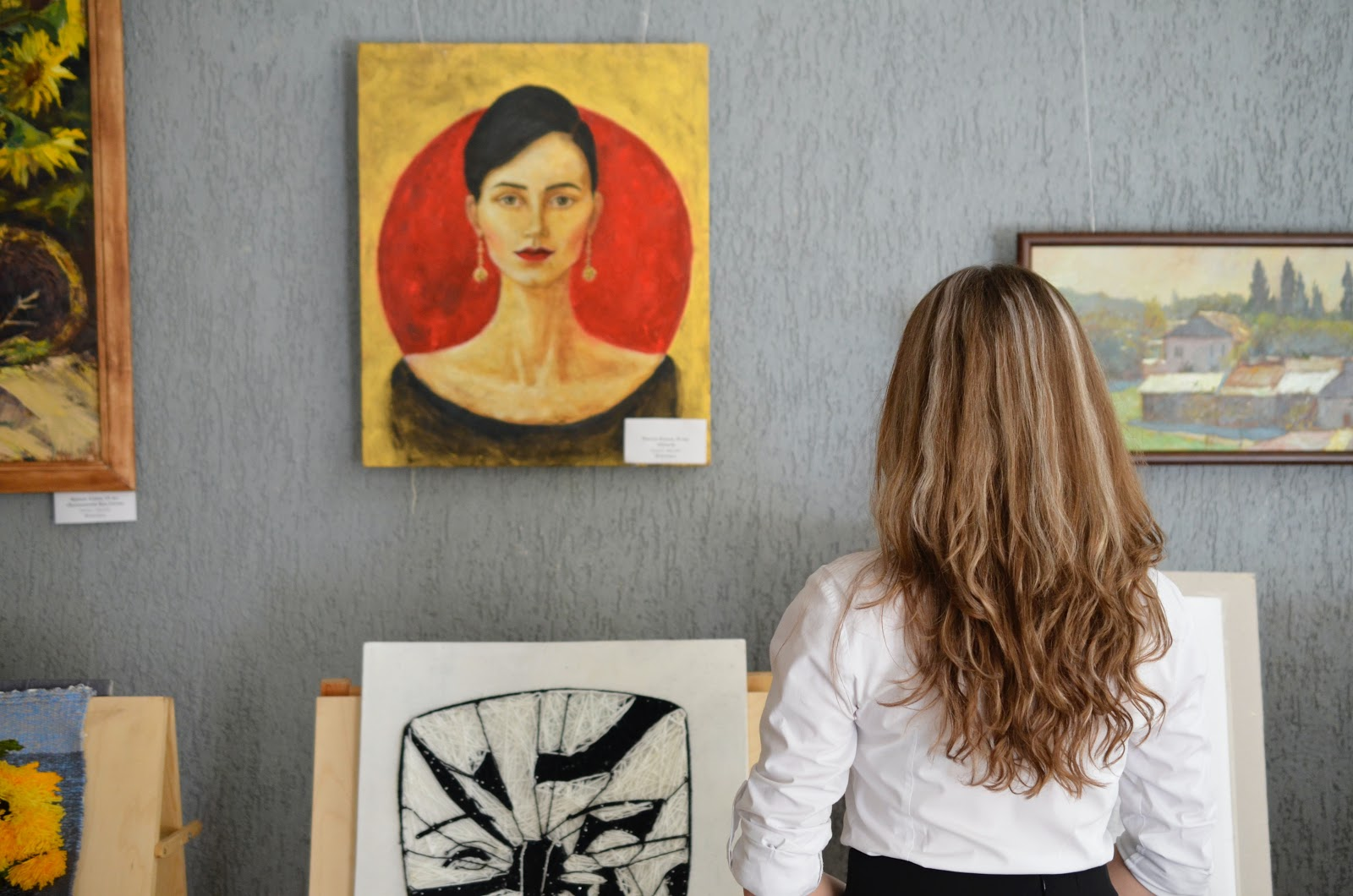 A woman views a painting of another woman in front of a yellow and orange background.