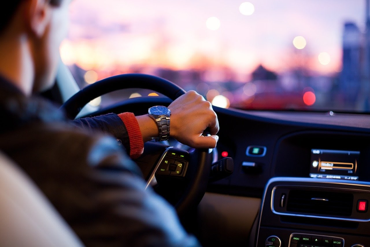 A man wearing a silver watch drives his car at dusk.