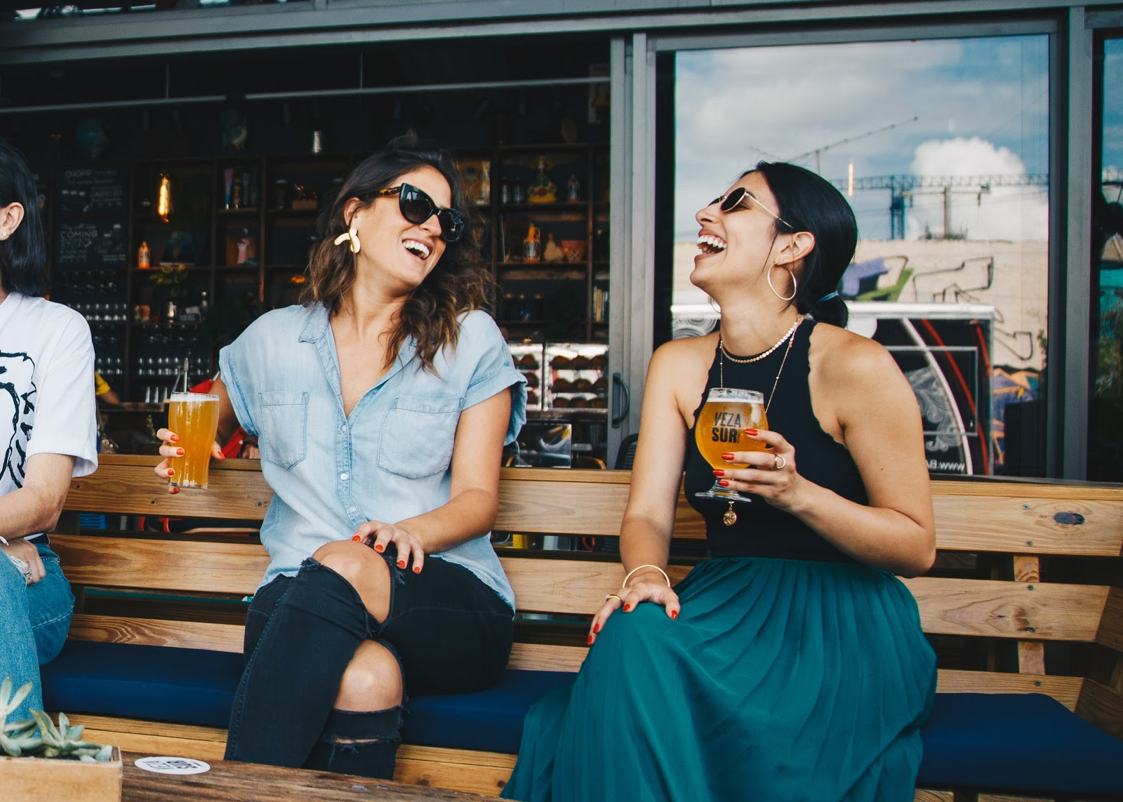 Two young women laugh on a bench while enjoying a drink of beer.
