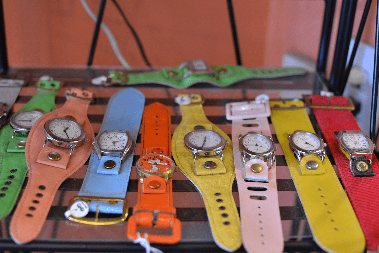 Eight colorful watches sit on a store shelf.
