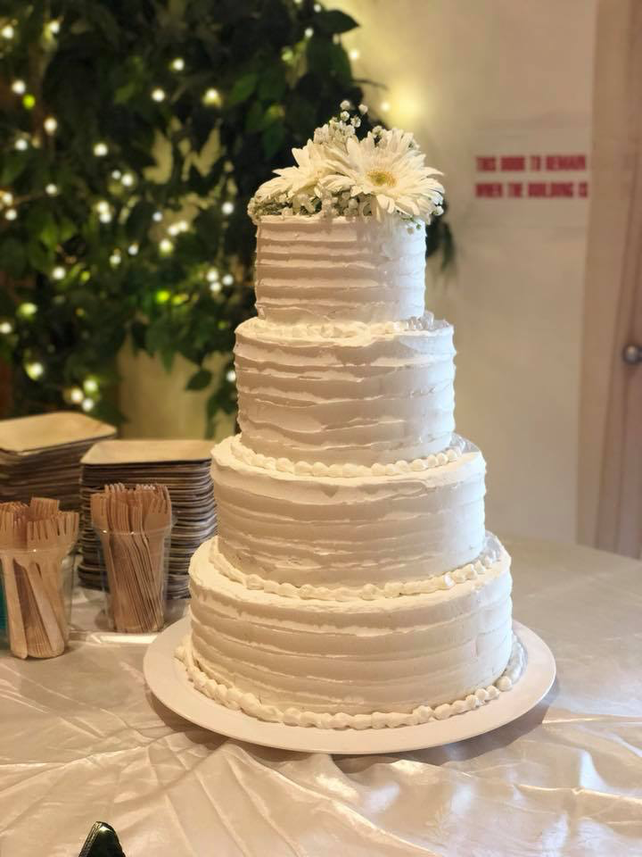 four tier wedding cake with flowers on top