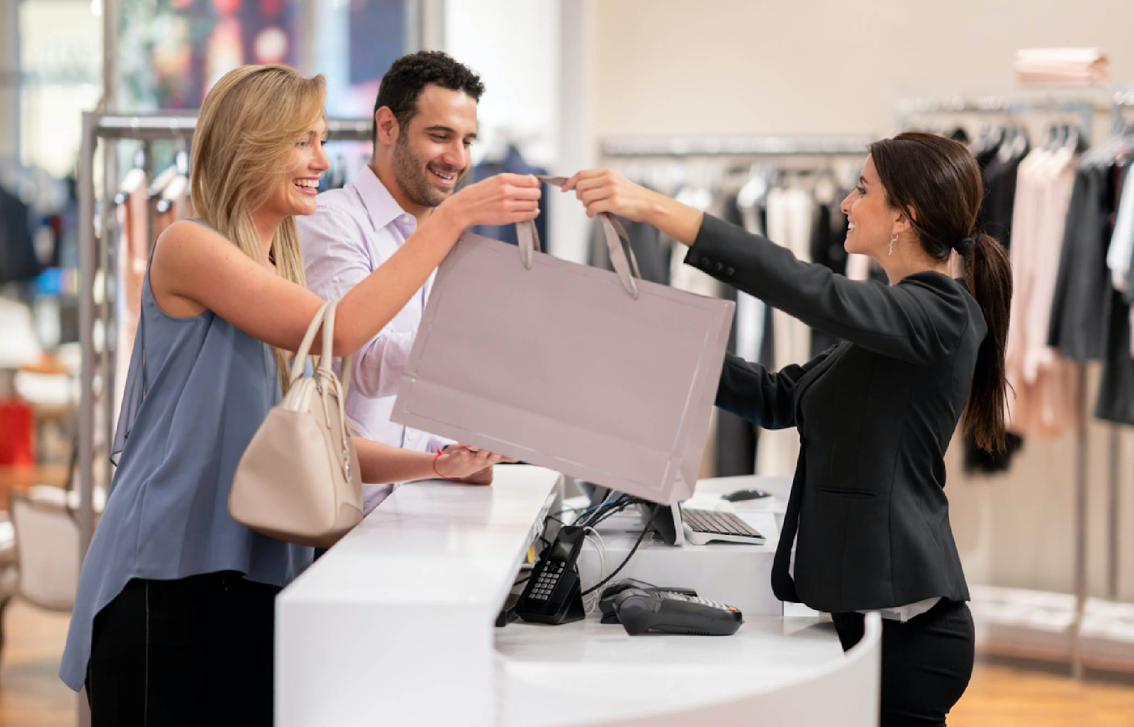 woman handing shopping bag to a couple over the counter
