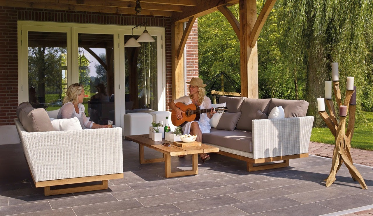 Two women on outdoor couches, one playing guitar