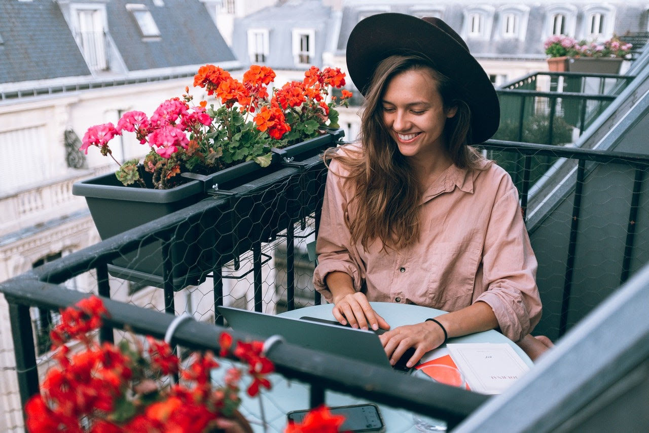 Woman typing on laptop on a balcony