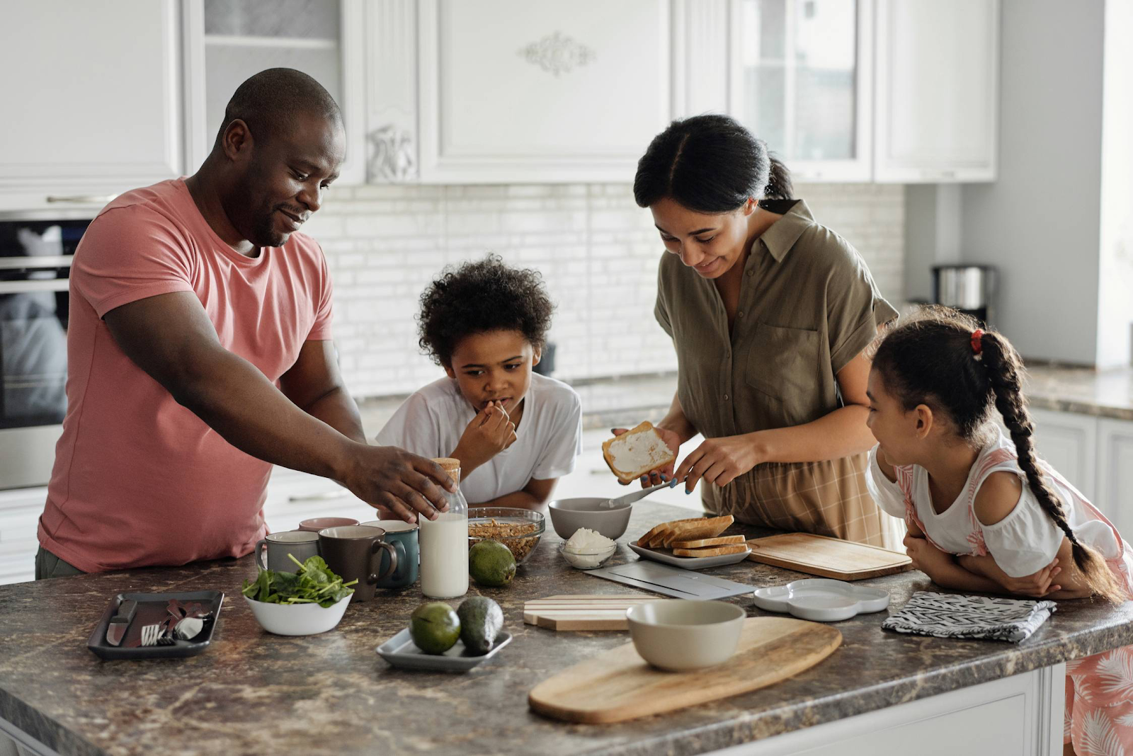 family at kitchen island making breakfast