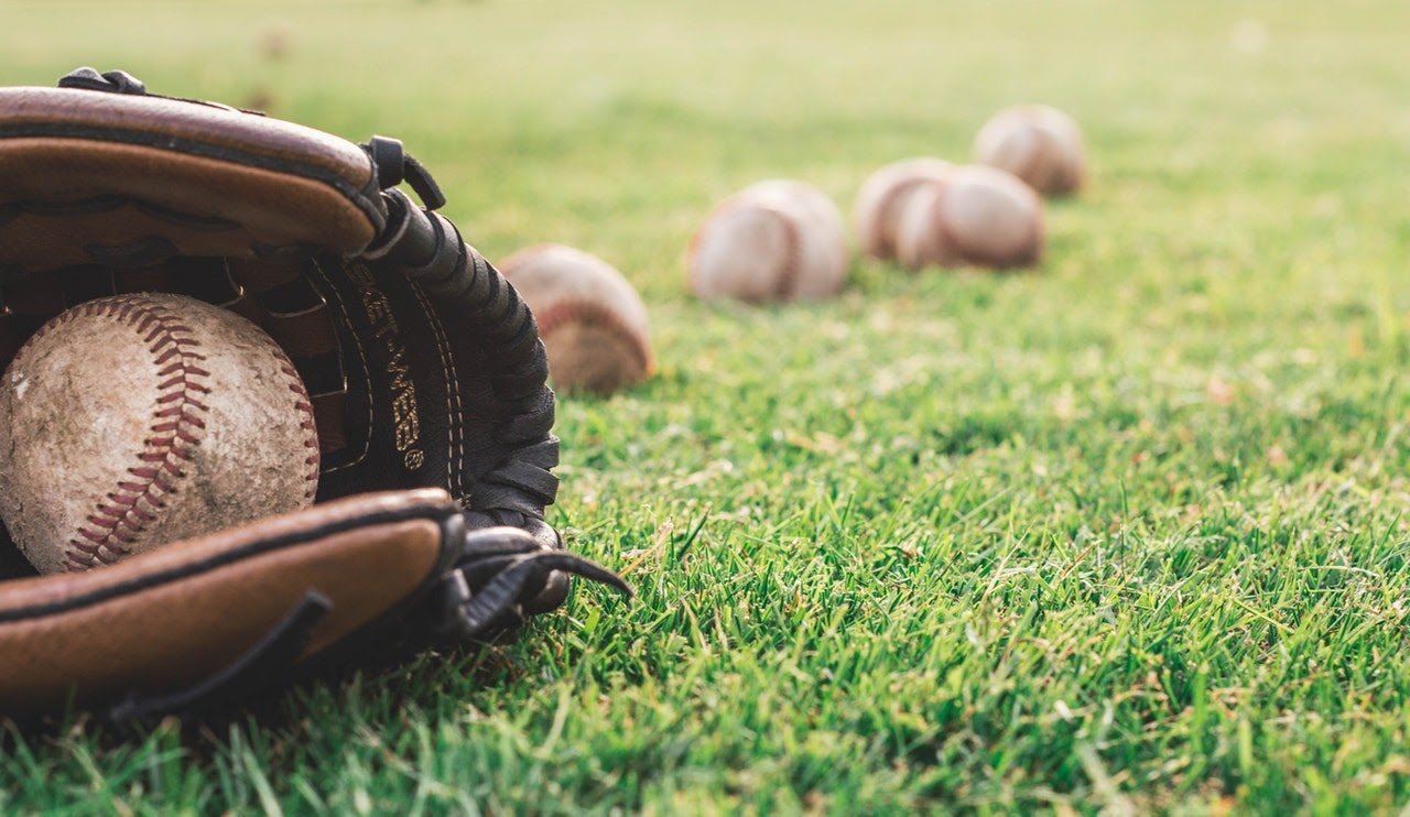 baseball in a glove on the grass