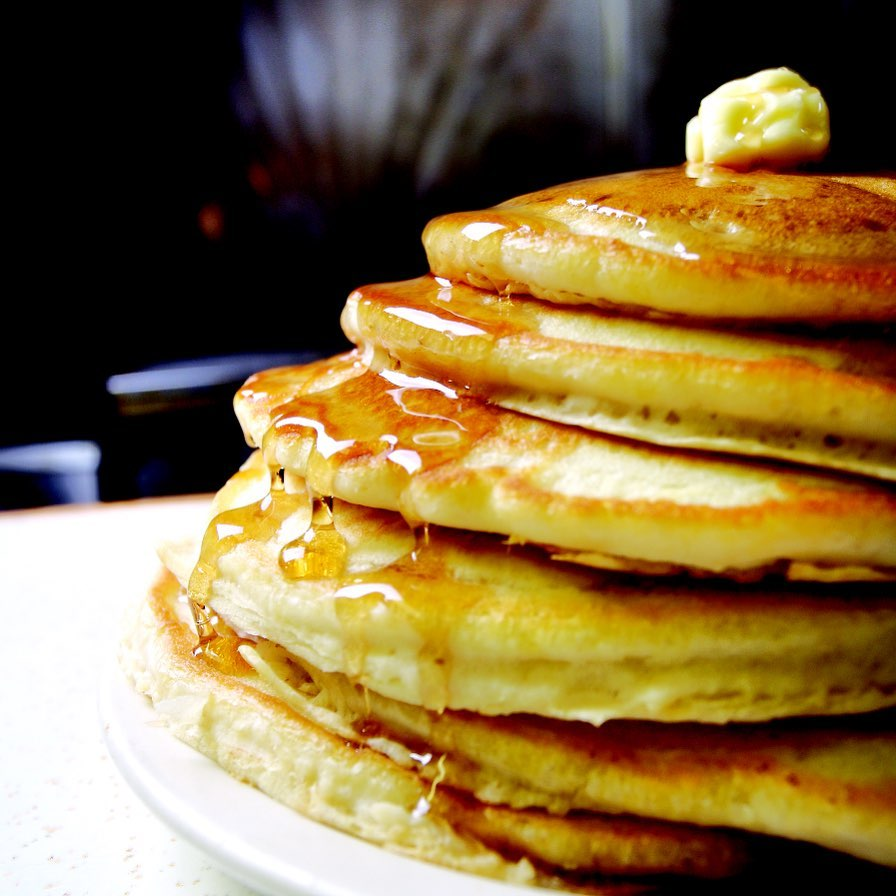 Pancakes with Butter and Maple Syrup on White Plate