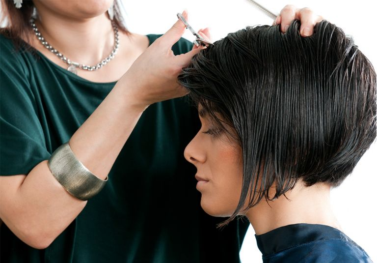Woman with dark hair getting bob cut.