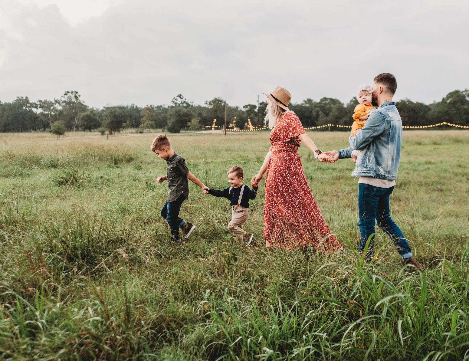 family holding hands and walking in a grassy field