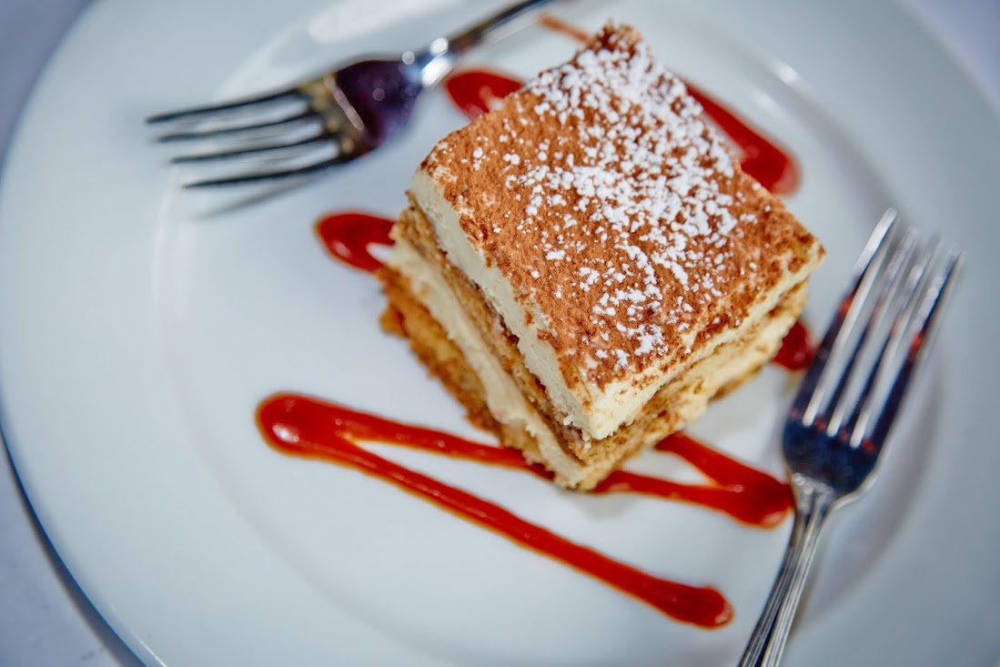 A Slice Of Tiramisu Resting On Top Of A Drizzle Of Strawberry Sauce