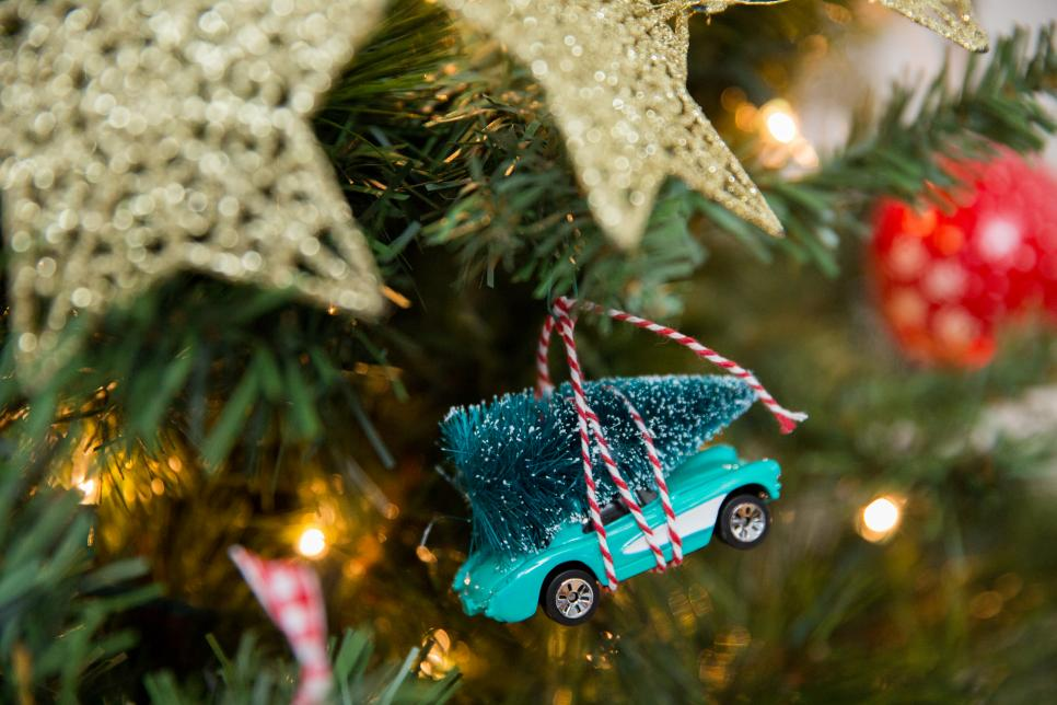 A Toy Vintage Car With Twine Wrapped Around A Christmas Tree On Roof