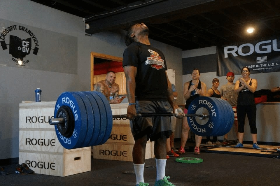 Man powerlifting as group cheers him on