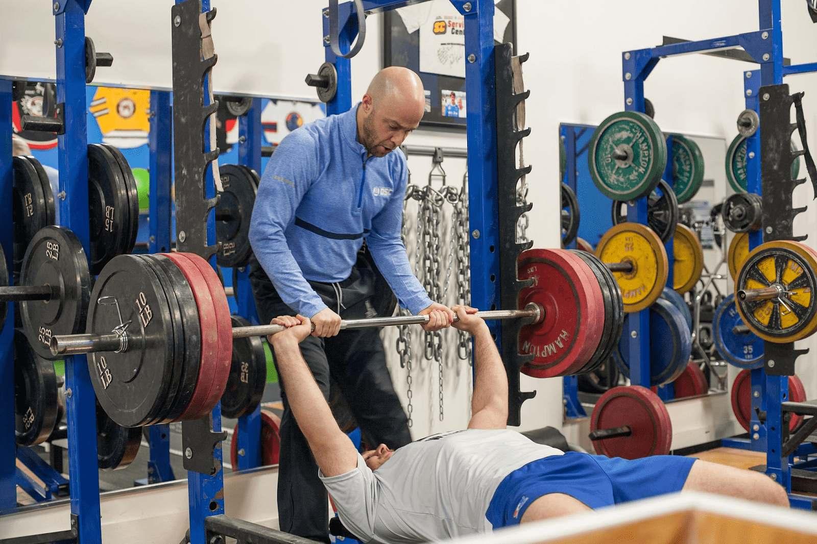 Trainer spotting man bench pressing