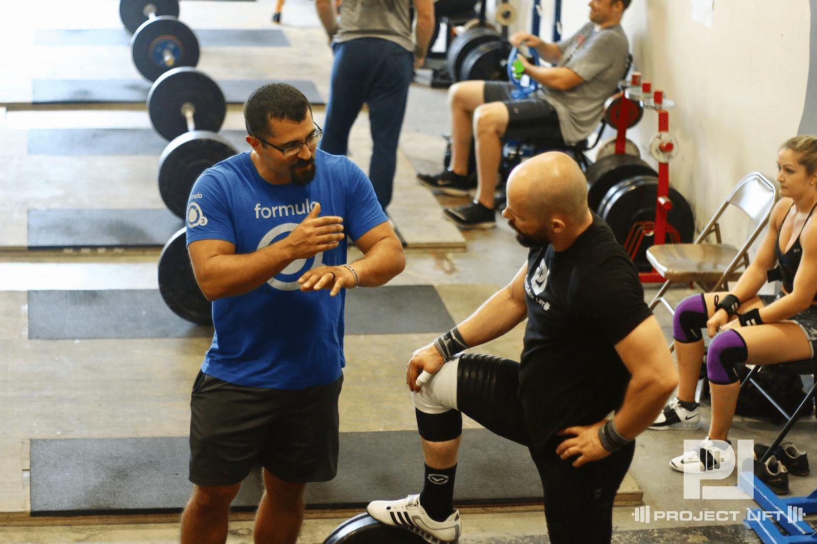 Men discussing lifting at gym