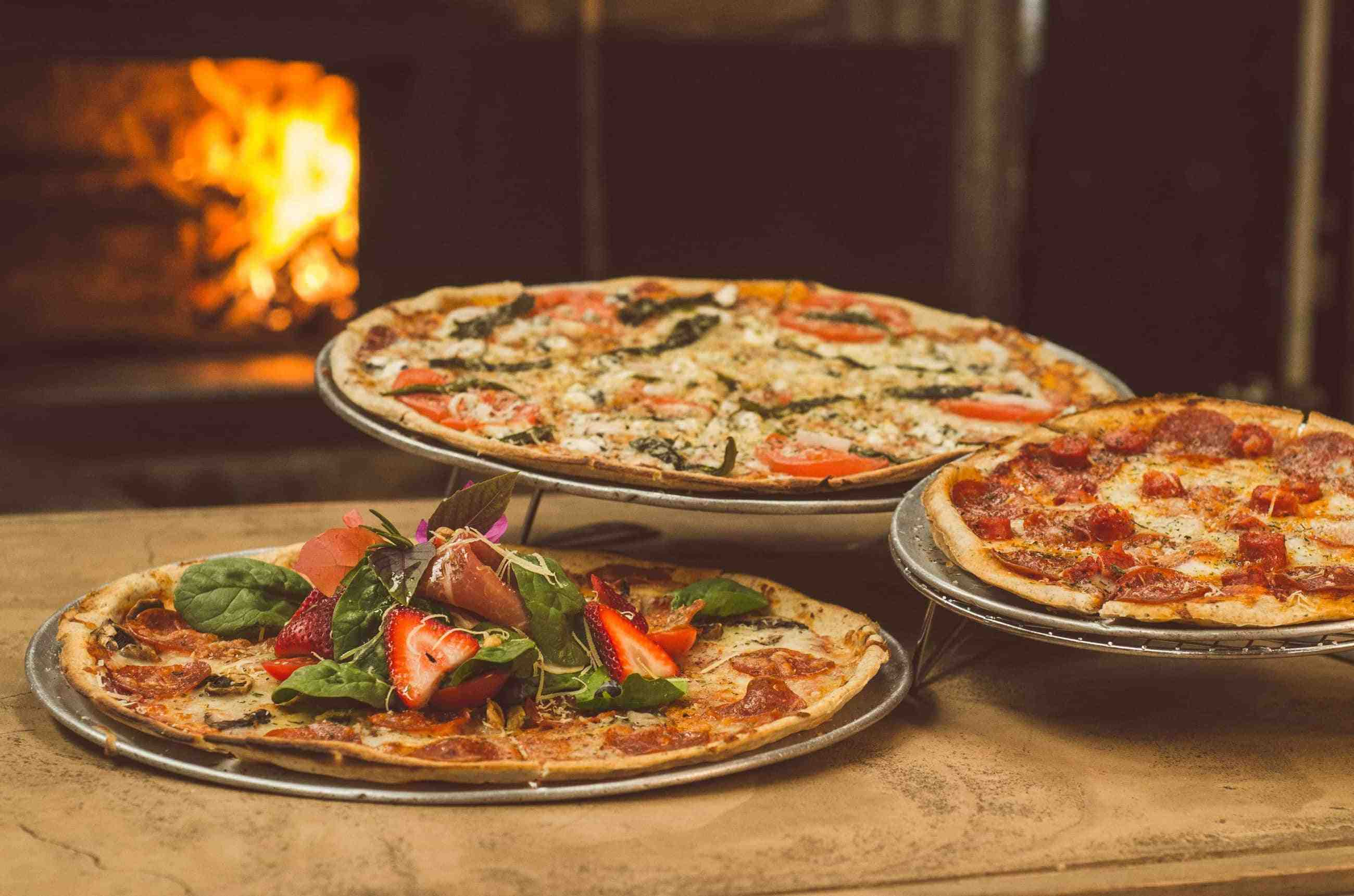 three pizzas in front of a brick pizza oven