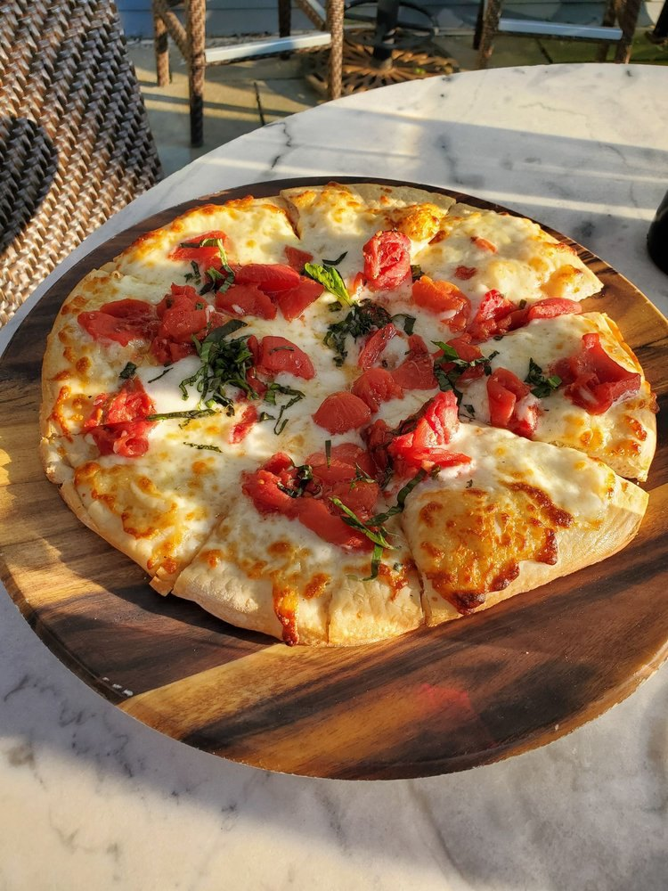 Margherita Pizza on outdoor table. Pizza is topped with cheese, basil, and tomatoes.