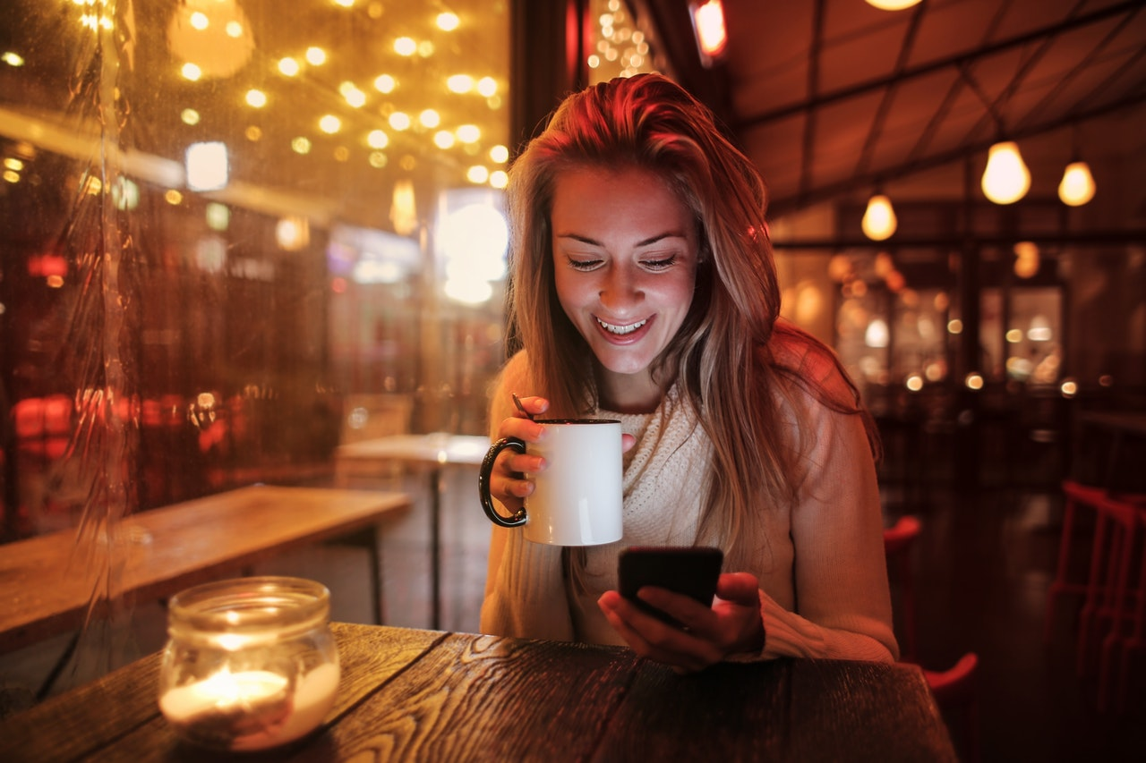 Woman enjoys cup of coffee at night in a coffee shop
