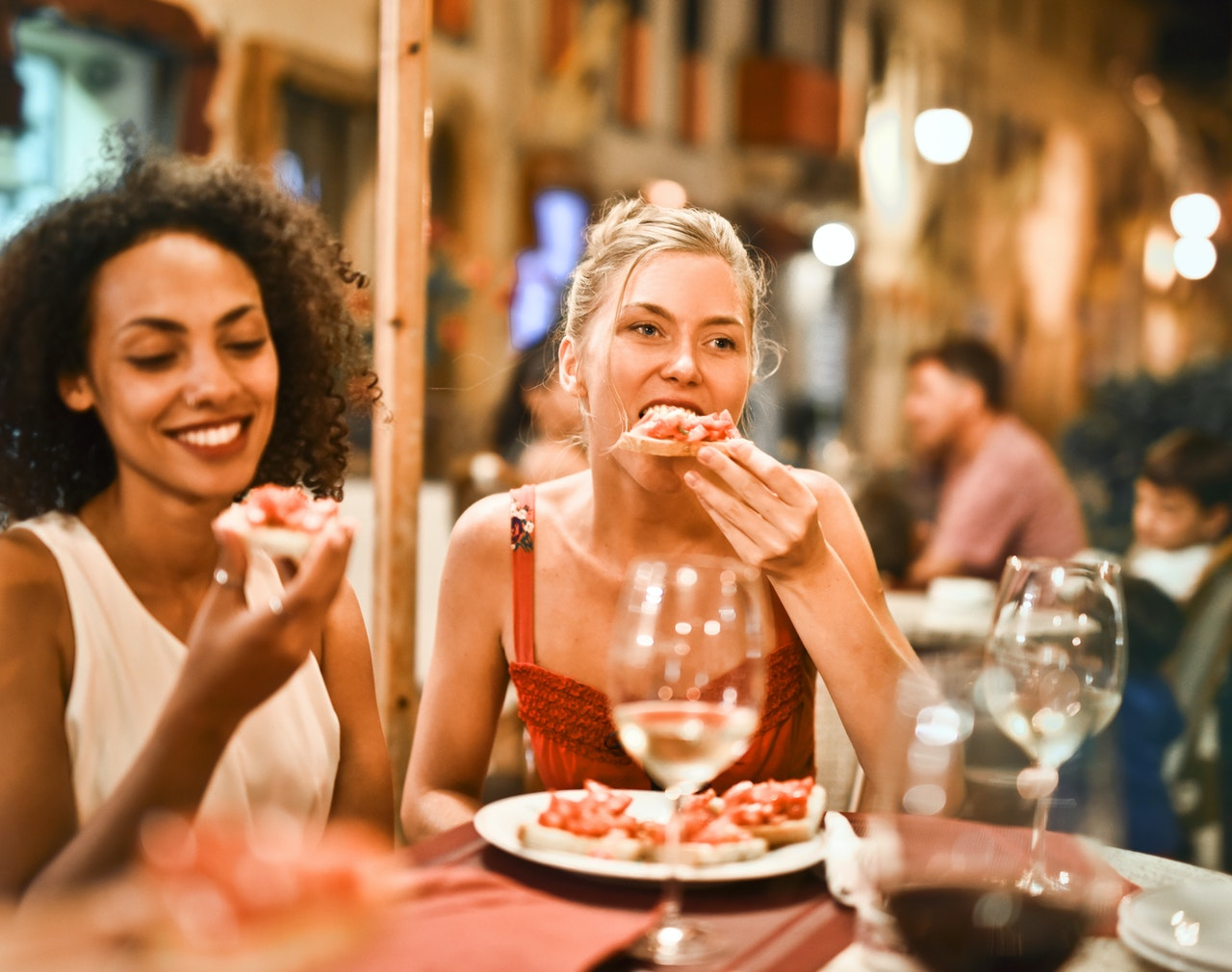 Two female friends smile and eat pizza in an outdoor eating area